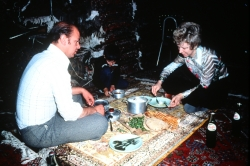 Mansour's uncle David enjoys a meal on an antique rug of his own